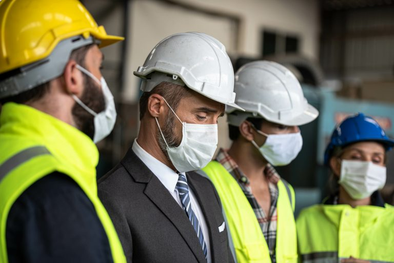 Industrial Manager and Technician, Engineer workers with hardhats, vest discussing Business Management in industry manufacturing Factory. They wear protective face mask for prevention covid 19